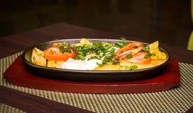 Pommes de terre et oeufs au plat avec des tomates et des verts Images libres de droits