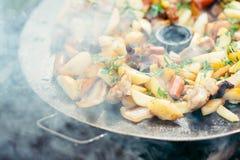Pommes de terre frites avec de la viande et des saucisses grillant le concept faisant cuire sur un feu ouvert Pique-nique le week Images libres de droits