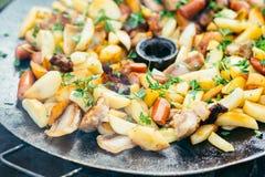Pommes de terre frites avec de la viande et des saucisses grillant le concept faisant cuire sur un feu ouvert Pique-nique le week Photo stock