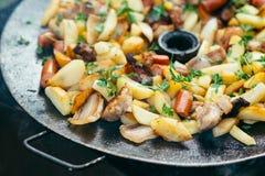 Pommes de terre frites avec de la viande et des saucisses grillant le concept faisant cuire sur un feu ouvert Pique-nique le week Images stock