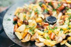 Pommes de terre frites avec de la viande et des saucisses grillant le concept faisant cuire sur un feu ouvert Pique-nique le week Photo libre de droits