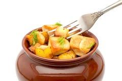 Pommes de terre frites avec des gros morceaux de viande dans un pot avec une fin de fourchette sur un fond blanc Image libre de droits