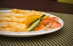 Pommes de terre frites avec des poivrons, des tomates et le concombre Photographie stock libre de droits