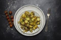 Pommes de terre frites avec les champignons et l'oignon dans le plat blanc au fond noir Fourchette et tomates-cerises près image libre de droits