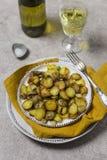 Pommes de terre frites avec les champignons et l'oignon dans le plat blanc avec la vigne au fond gris pour le dîner de vacances photo stock
