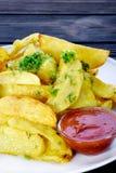 Pommes de terre frites coupées en tranches avec les herbes fraîches image stock