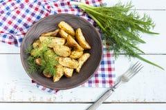 Pommes de terre frites cuites au four délicieuses avec l'aneth dans le plat blanc sur la table Image libre de droits