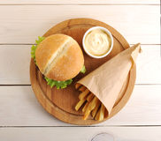 Pommes de terre frites dans un sac de papier, une sauce au fromage et un hamburger Image stock