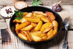 Pommes de terre frites dans une casserole de fonte images libres de droits