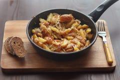 Pommes de terre frites dans une poêle avec du pain de seigle Photos stock