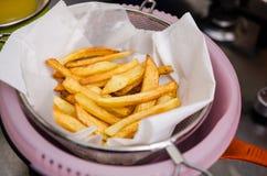 Pommes de terre frites s'écoulant sur la serviette de papier Photographie stock libre de droits
