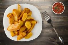 Pommes de terre de friture sur un fond en bois Photo stock