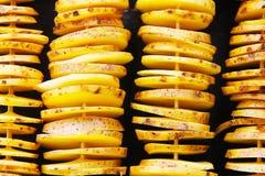 Pommes de terre jaunes crues dans une peau, coupe en tranches Des morceaux sont ficelés sur les brochettes en bois, présentées da Photographie stock libre de droits