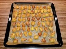 Pommes de terre rôties sur le papier de cuisson dans le plateau de cuisson photos libres de droits