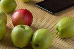 Pommes dispersées sur une table en bambou légère Est tout près le compu de comprimé Photos libres de droits