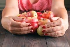 Pommes douces de prise de femme sur le fond en bois Photo stock