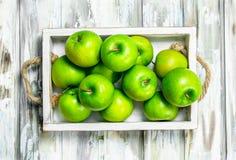 Pommes entières juteuses vertes dans une boîte en bois photo stock