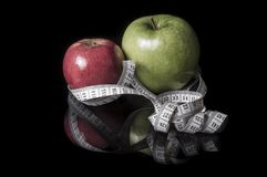Pommes entourées avec la bande de mesure sur le noir avec la réflexion Photo libre de droits