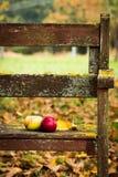 Pommes et feuilles sur un banc dans le verger Photo stock