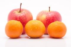 Pommes et mandarines rouges avec des waterdrops sur le blanc Photos stock
