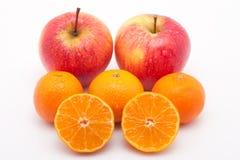 Pommes et mandarines rouges avec des waterdrops sur le blanc Photographie stock