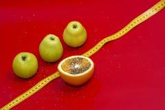 Pommes et orange qu'une mesure attachent du ruban adhésif sur un fond rouge images libres de droits