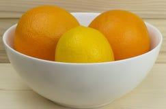 Pommes et oranges naturelles juteuses fraîches dans un plat blanc brillant sur le fond en bois Photographie stock libre de droits