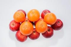 Pommes et oranges rouges sur le blanc Photographie stock