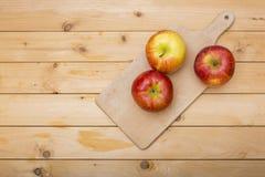 Pommes et plat étripant en bois sur le fond en bois Photo stock