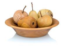 Pommes et poires en bois dans un bol de fruit fait à partir de l'différents types de bois d'isolement sur le fond blanc avec la r photos stock