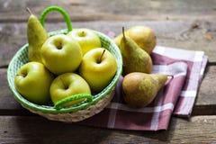 Pommes et poires vertes fraîches sur une table en bois Photos stock