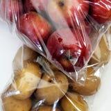 Pommes et pommes de terre dans des sacs de cellophane Photographie stock libre de droits
