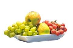 Pommes, et raisins d'une plaque, sur le blanc Image libre de droits