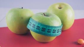 Pommes et sucreries sur une table en bois blanche Nourriture néfaste et saine sur un fond blanc photos stock