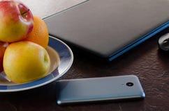 Pommes et téléphone intelligent sur la table à côté de l'ordinateur portable Image stock