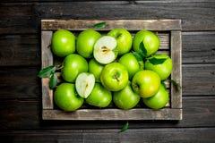 Pommes et tranches vertes juteuses d'Apple dans une boîte en bois image libre de droits