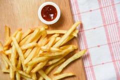 Pommes-Frites auf hölzernem Brett mit Speisetische des Ketschups lizenzfreie stockfotografie