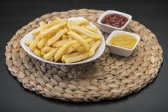 Pommes-Frites auf Tabellenmatte mit Ketschup- u. Senfsoße Stockfoto