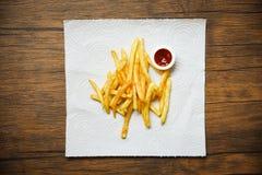Pommes-Frites auf Weißbuch mit hölzernem Hintergrund des Ketschups stockbild