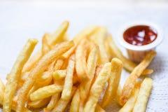 Pommes-Frites auf Weißbuch mit Speisetische des Ketschups lizenzfreie stockfotos
