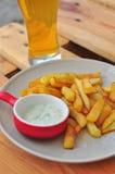Pommes frites avec de la sauce et la bière à ail Image libre de droits