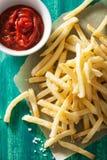 Pommes frites avec le ketchup au-dessus du fond vert Photographie stock