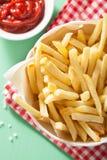 Pommes frites avec le ketchup au-dessus du fond vert Photos stock