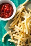 Pommes frites avec le ketchup au-dessus du fond vert Images libres de droits
