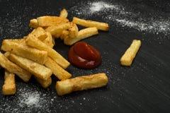 Pommes frites avec le ketchup sur le fond foncé image libre de droits