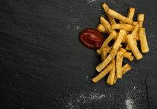 Pommes frites avec le ketchup sur le fond foncé photo stock