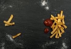 Pommes frites avec le ketchup sur le fond foncé image stock