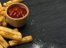 Pommes frites avec le ketchup sur le fond foncé photos stock