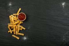 Pommes frites avec le ketchup sur le fond foncé photographie stock