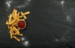 Pommes frites avec le ketchup sur le fond foncé images stock